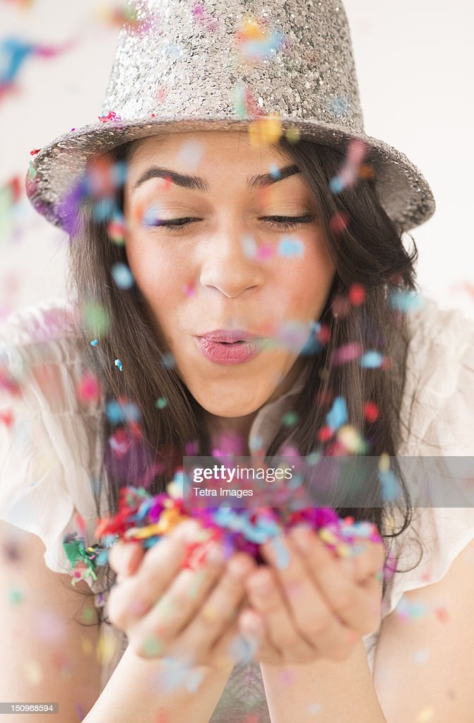Portrait of young woman blowing confetti