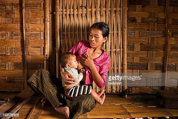 Portrait of young woman breastfeeding her baby in Northern Laos