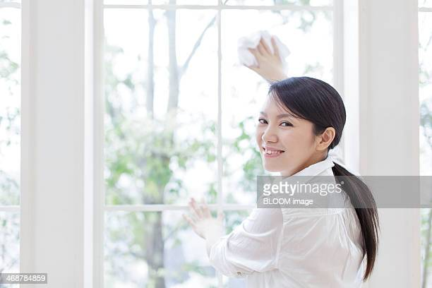 Portrait of young woman cleaning window
