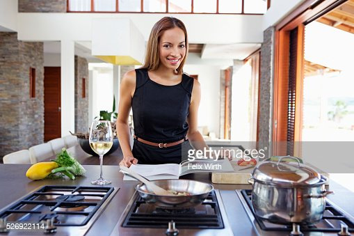 Portrait of young woman cooking dinner : ストックフォト