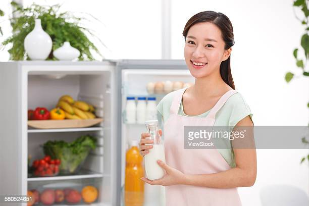 Portrait of young woman cooking in kitchen