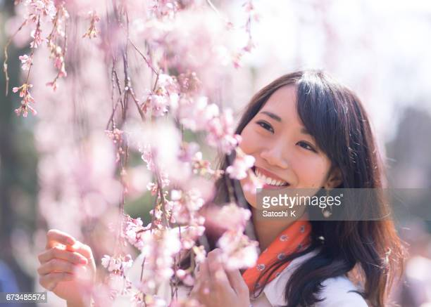 Portrait of young woman covered with plum blossoms