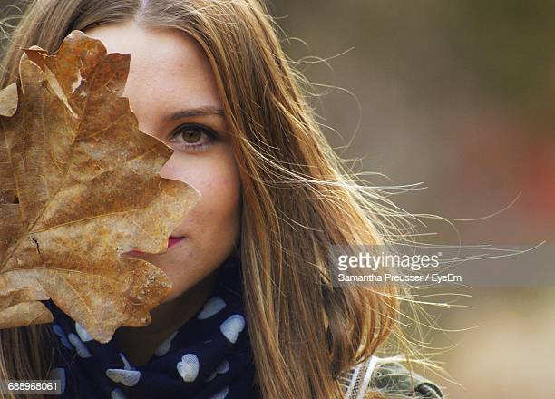 Portrait Of Young Woman Covering Face With Dry Leaf
