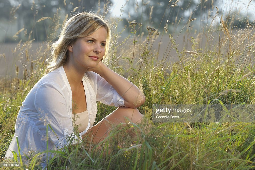 Portrait of young woman daydreaming in a field : Stock Photo