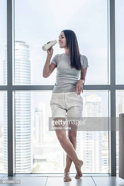 Portrait of young woman drinking milk in front of window