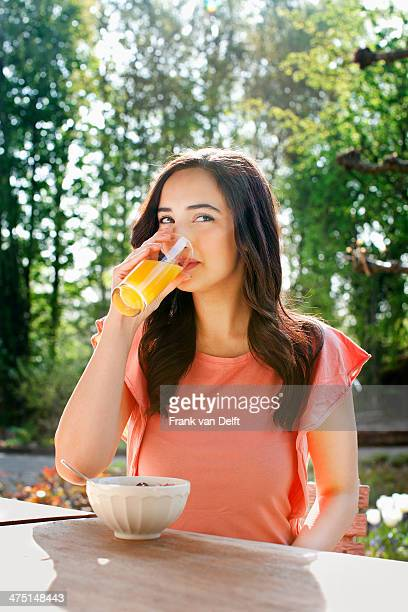 Portrait of young woman drinking orange juice in garden