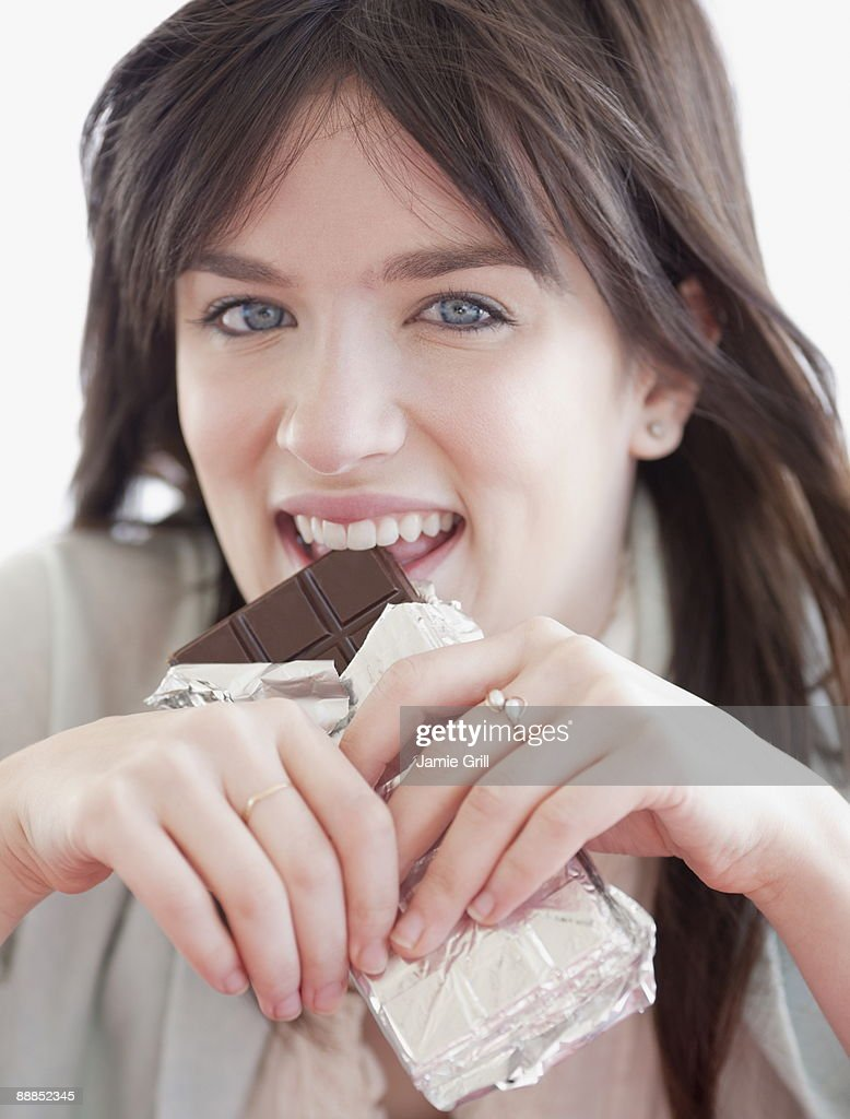 Portrait of young woman eating chocolate : Stock Photo