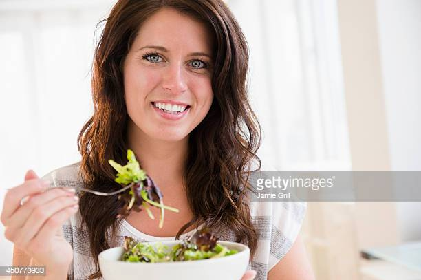 Portrait of young woman eating fresh salad