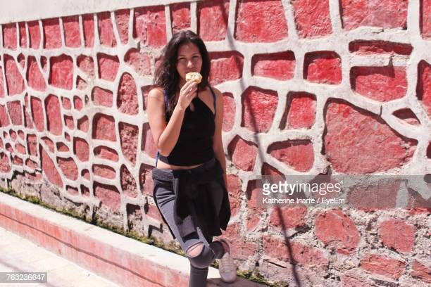 Portrait Of Young Woman Eating Ice Cream While Standing By Wall On Sunny Day