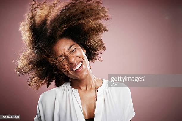 Portrait of young woman flicking hair, smiling