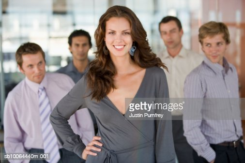 Portrait of young woman, four men in background looking at her : Stock Photo