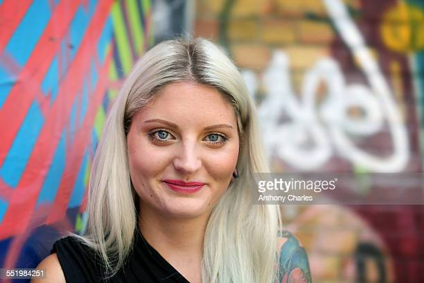Portrait of young woman, graffiti in background