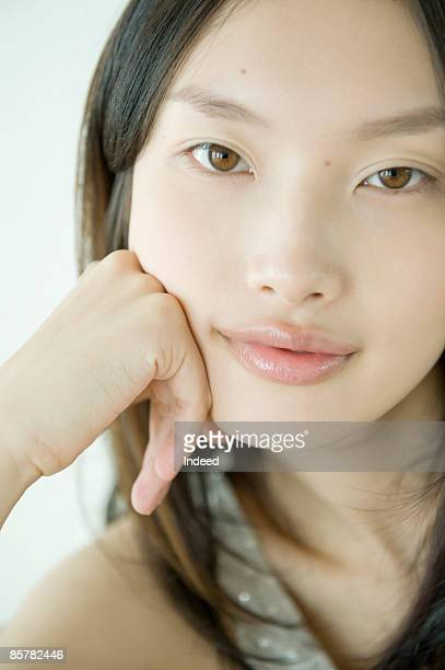 Portrait of young woman, hand on chin, close up