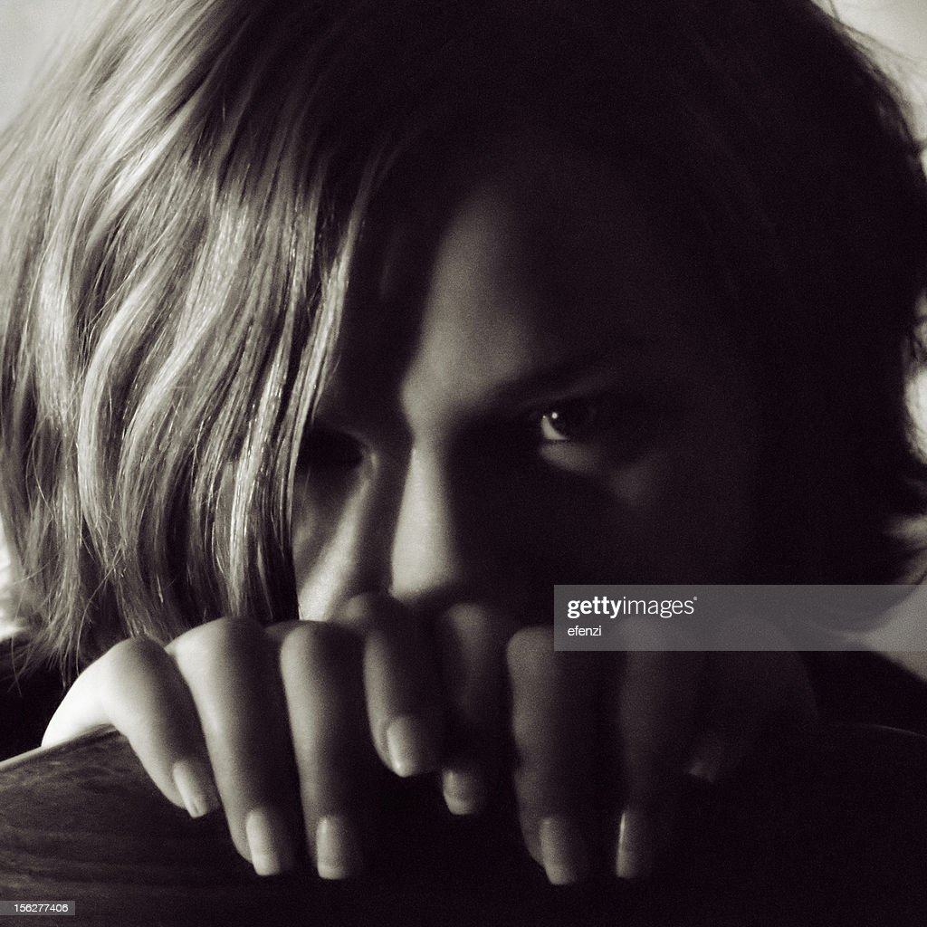 Portrait of Young Woman Hiding Behind Chair, Low Key : Stock Photo