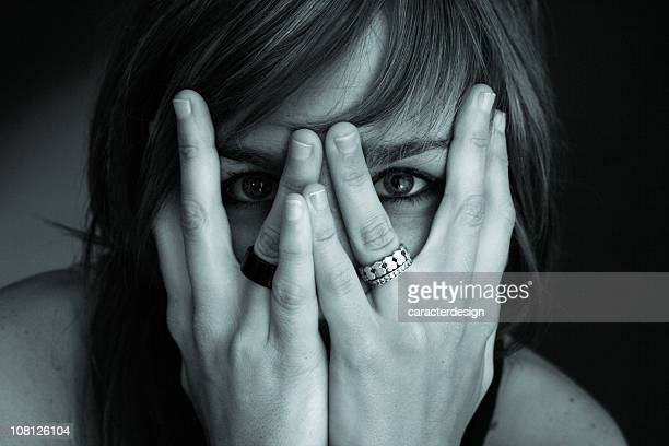 Portrait of Young Woman Hiding Face in Hands, Toned