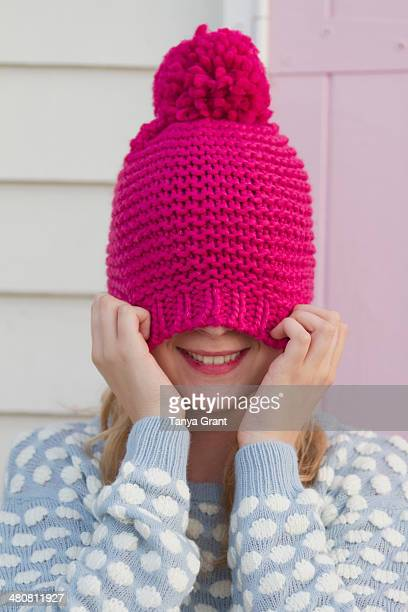 Portrait of young woman hiding under wooly hat