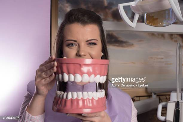 Portrait Of Young Woman Holding Anatomical Model Of Teeth