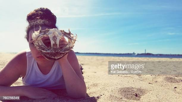 Portrait Of Young Woman Holding Animal Skull While Lying At Beach Against Sky During Sunny Day