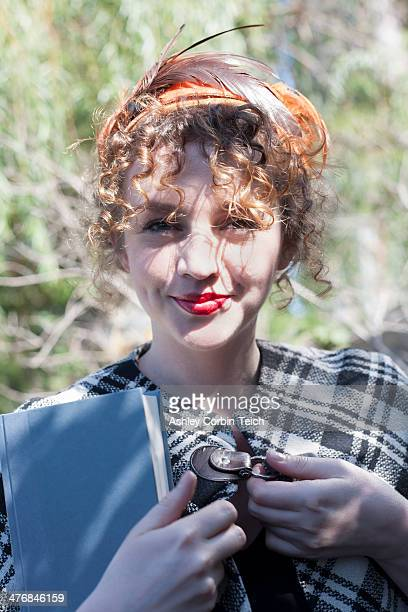 Portrait of young woman holding book in park