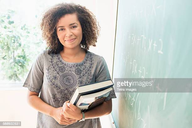 Portrait of young woman holding books