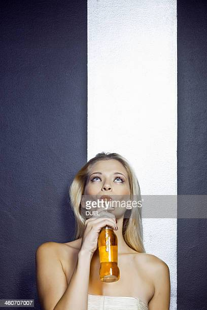 Portrait of young woman holding bottle of beer