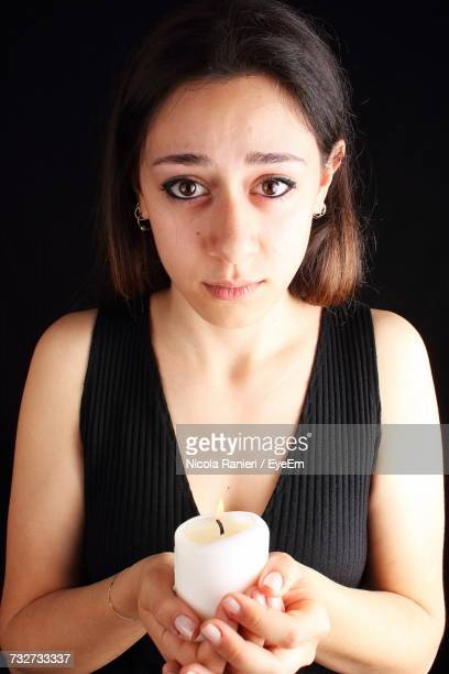 Portrait Of Young Woman Holding Candle Against Black Background