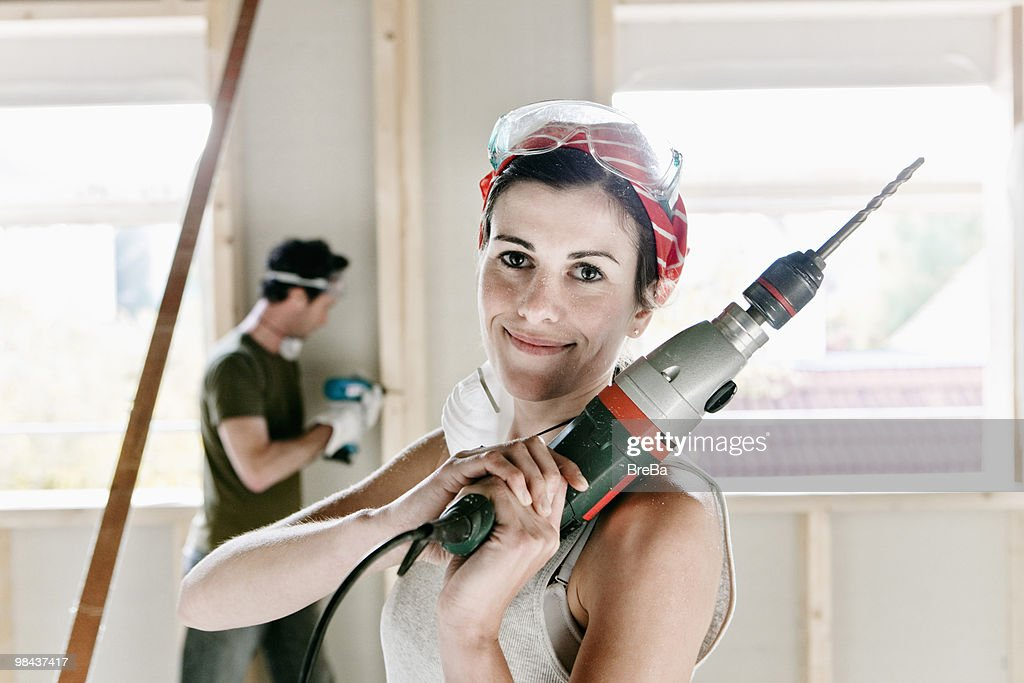 portrait of young woman holding electric drill