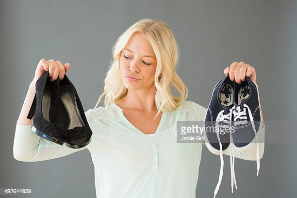 Portrait of young woman holding shoes, Jersey City, New Jersey, USA