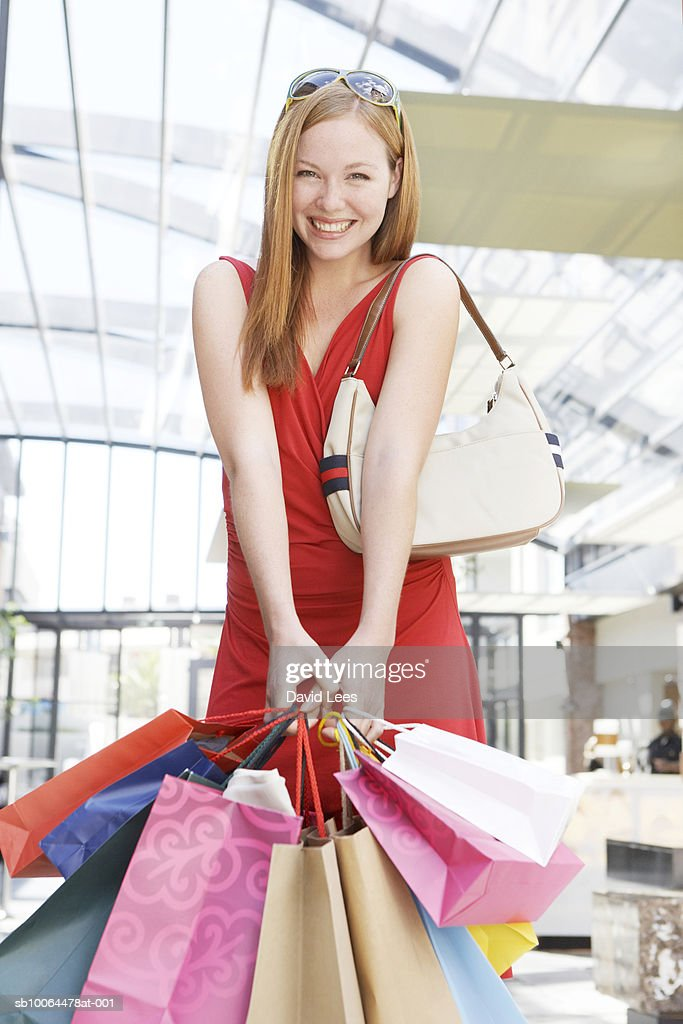 Portrait of young woman holding shopping bags, smiling : Stock Photo