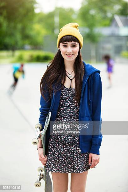 Portrait of young woman holding skateboard