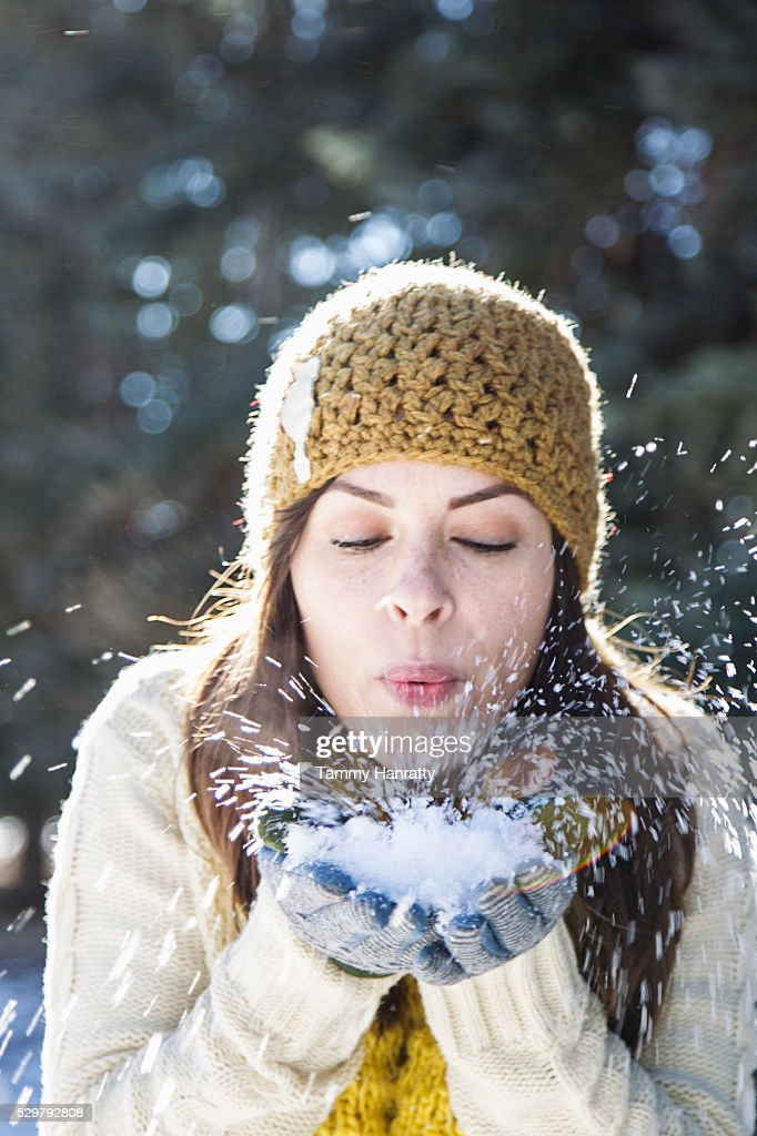 Portrait of young woman holding snow and blowing it : Stock Photo