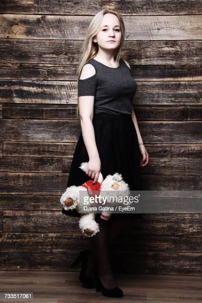 Portrait Of Young Woman Holding Teddy Bear While Standing Against Wooden Wall