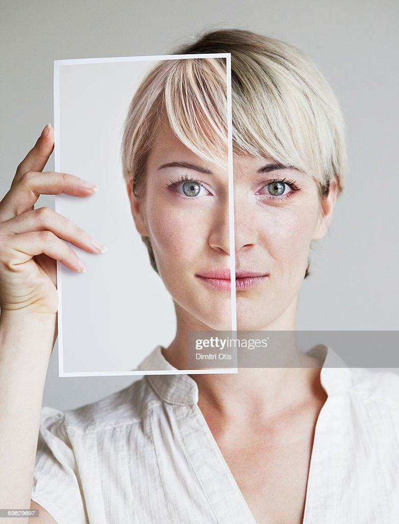 Portrait of young woman holding up a her picture : Stock Photo