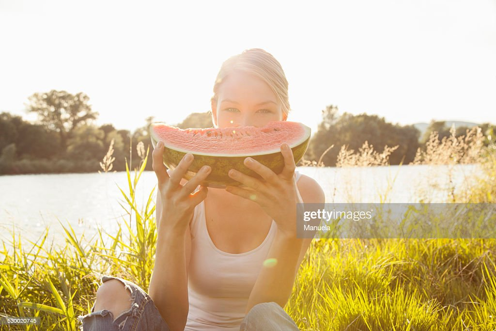 Portrait of young woman holding up melon slice in front of face, Danube Island, Vienna, Austria