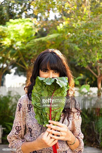 Portrait of young woman holding vegetable leaf