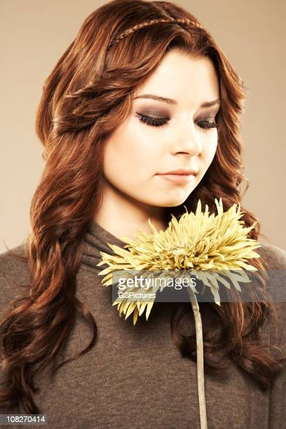 Portrait of Young Woman Holding Yellow Flower