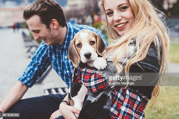 Portrait of young woman hugging cute dog, Lake Como, Italy