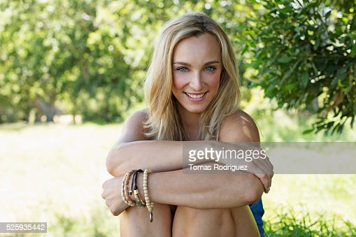 Portrait of young woman hugging knees : Stock Photo