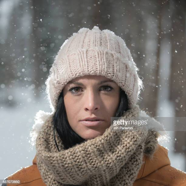 Portrait of Young Woman in a Forest Wearing Layers of Winter Clothing during a Snowstorm