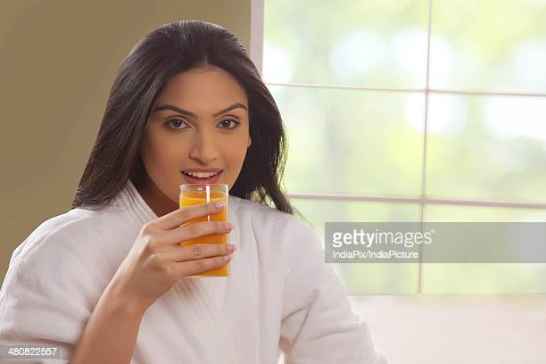 Portrait of young woman in bathrobe having mango juice at home