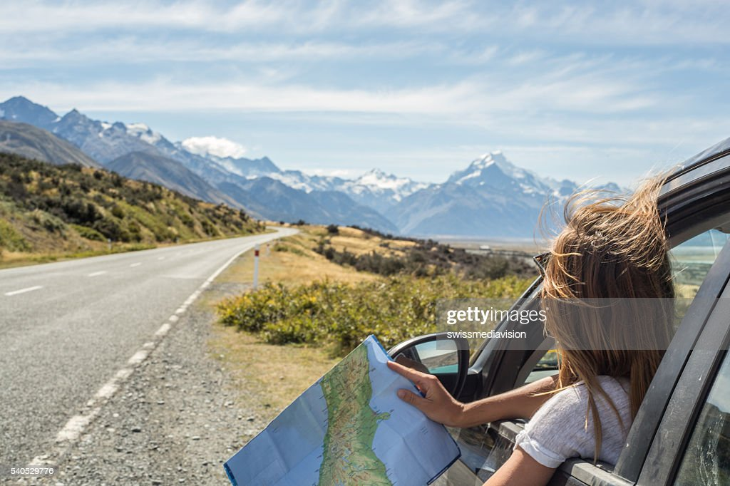 Portrait of young woman in car looking at map : Stock Photo