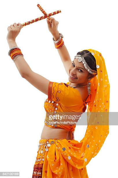 Portrait of young woman in chaniya choli performing Dandiya Raas over white background