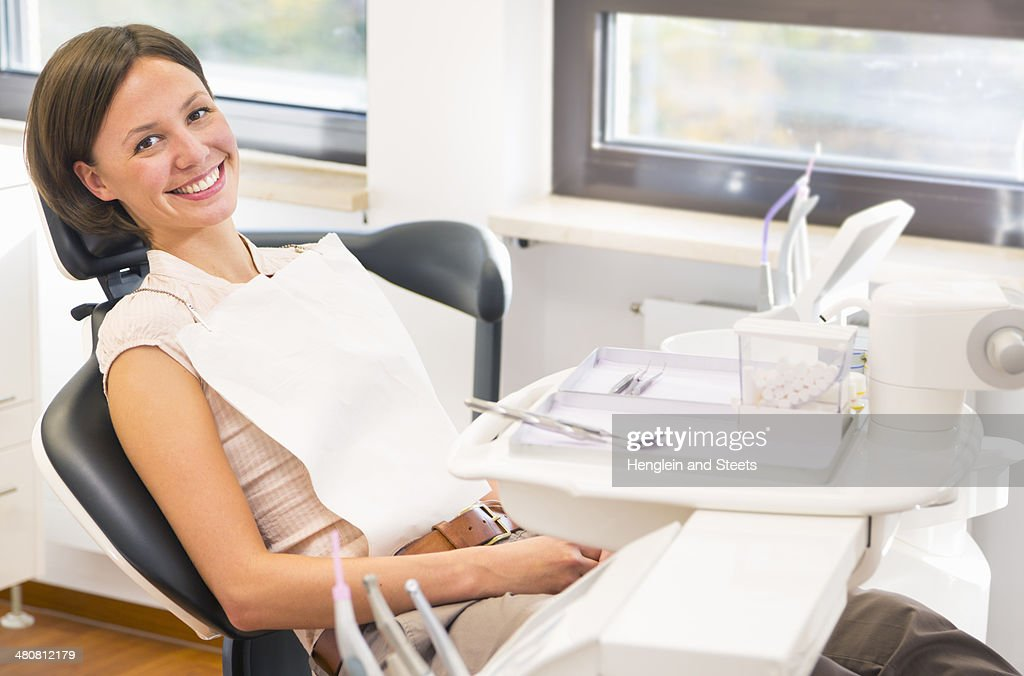 Portrait of young woman in dentists chair, smiling