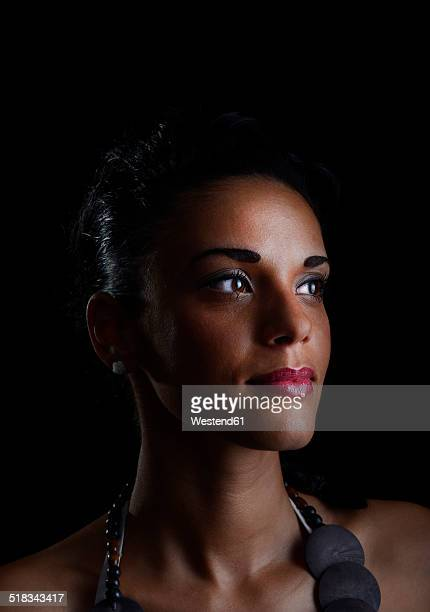 Portrait of young woman in front of black background