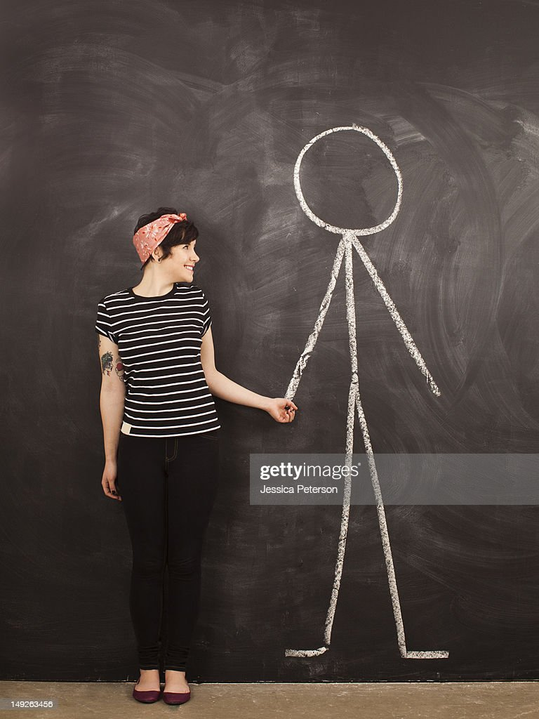 Portrait of young woman in front of blackboard : Stock Photo