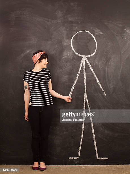 Portrait of young woman in front of blackboard