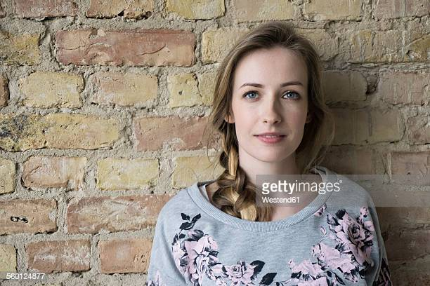 Portrait of young woman in front of brick wall