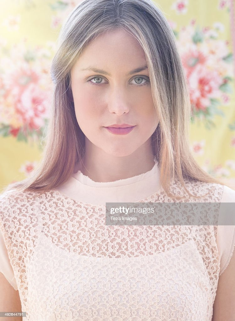 Portrait of young woman in front of floral wall paper, Jersey City, New Jersey, USA