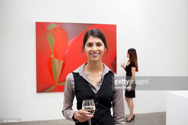 Portrait of young woman in front of painting in art gallery