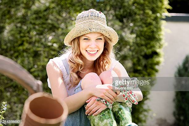 portrait of young woman in garden wearing straw hat